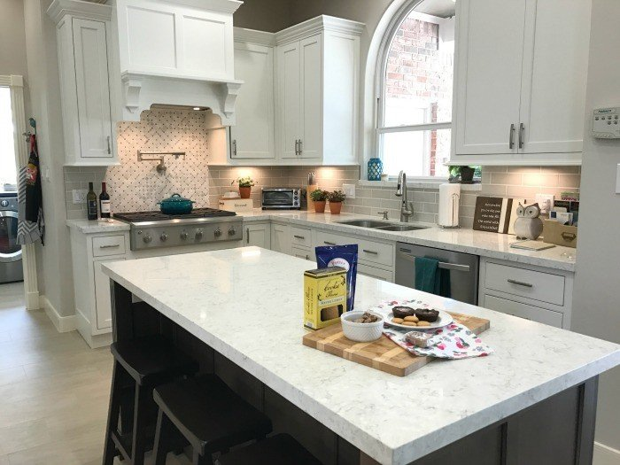 Kitchen Remodel Before and After Photos using White Cabinets, Stained Wood Island, and Marble Look Quartz Counters. Plus, how to change the layout and plan a kitchen remodel with good flow for your family before your remodel.  #AbbottsAtHome #KitchenRemodel #KitchenUpdate #KitchenMakeover #KitchenDesign #KitchenIdeas #WhiteKitchen