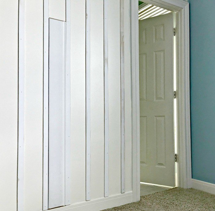 Lattice boards attached to wall with spacer as a guide. White DIY Board and Batten Wainscoting with lattice. Wainscoting ideas with classic style and Farmhouse woodworking charm.