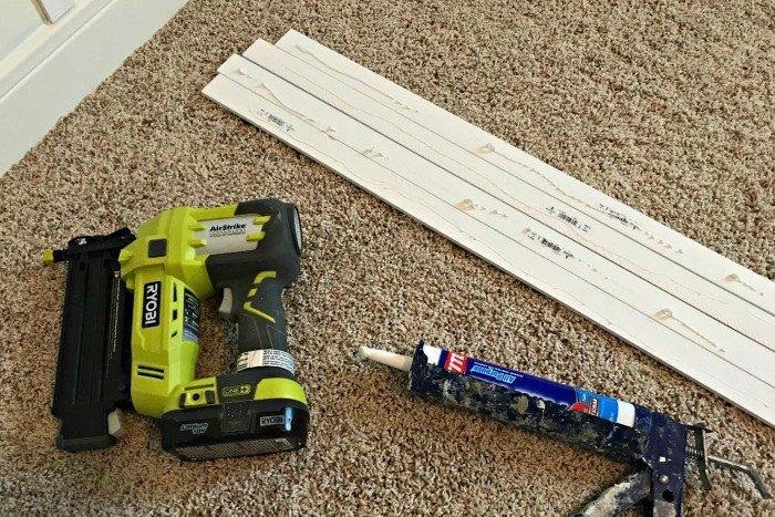 Adhesive on lattice, with brad nailer, and adhesive in caulk gun. White DIY Board and Batten Wainscoting with lattice. Wainscoting ideas with classic style and Farmhouse woodworking charm.