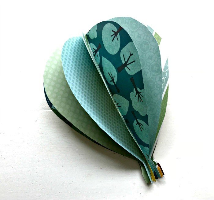One 3D paper hot air balloon craft on a white background. Learn How to Make Paper Hot Air Balloon Wall Art with cute double-sided scrap book paper. This tutorial is easy and works great on walls or as a mobile in a kid's room.