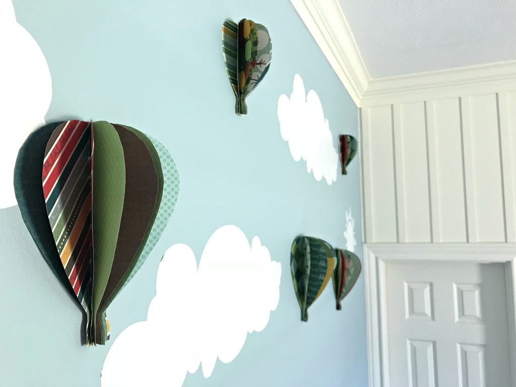 6 paper hot air balloons on a Magnolia paint blue wall with white clouds. Learn How to Make Paper Hot Air Balloon Wall Art with cute double-sided scrap book paper. This tutorial is easy and works great on walls or as a mobile in a kid's room.