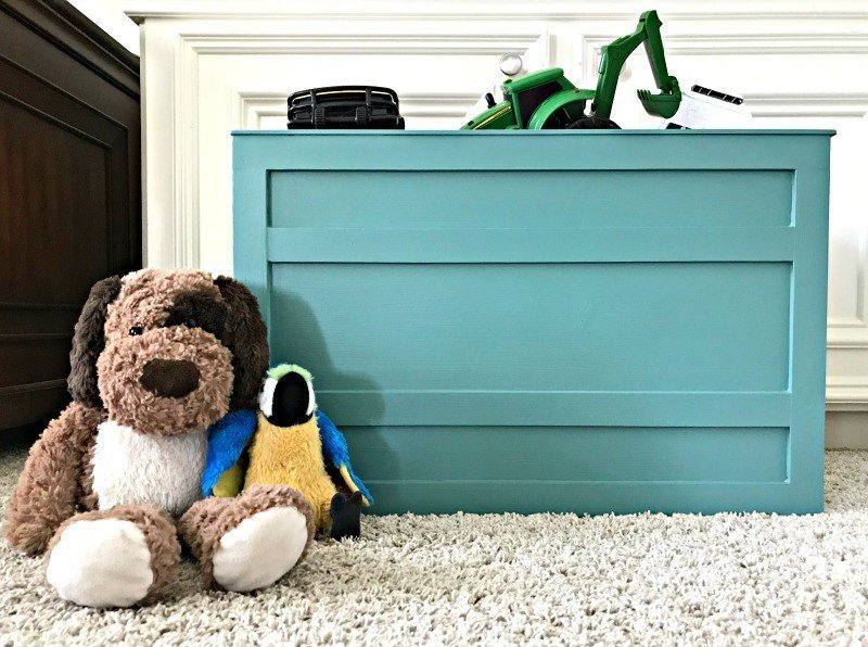 A fun teal large kids DIY wooden storage box. Kids playroom toy storage in a open DIY teal crate and a low dresser. Build a Modern Farmhouse DIY Wooden Toy Storage Crate or Box for all of those kids toys cluttering up your house. Makes a beautiful throw pillow and blanket box in a Living Room or catch all storage box for teens too! #AbbottsAtHome #StorageBox #ToyBox #DIYStorage