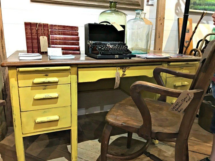 A yellow antique and distressed desk with wood top. The Spring and Fall Round Top Texas Antiques and Flea Markets are great! BUT you can find Fun, Art & Furniture Shopping in Round Top, Texas year round, guys! Check out photos from the shops in town. #RoundTop #TexasTravel #AbbottsAtHome