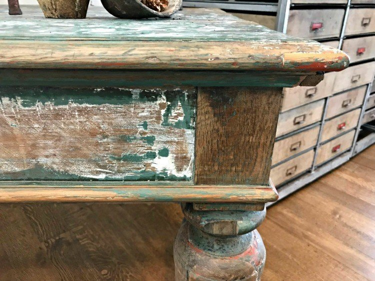Distressed and chippy white, green, and wood finish on a table. The Spring and Fall Round Top Texas Antiques and Flea Markets are great! BUT you can find Fun, Art & Furniture Shopping in Round Top, Texas year round, guys! Check out photos from the shops in town. #RoundTop #TexasTravel #AbbottsAtHome