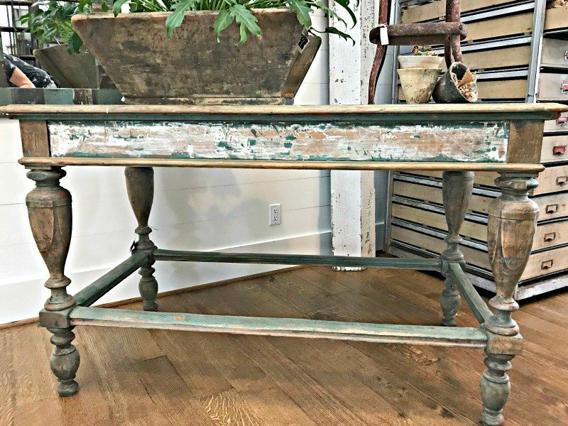 A distressed finish on a table with worn, exposed wood and chippy paint distressing. The Spring and Fall Round Top Texas Antiques and Flea Markets are great! BUT you can find Fun, Art & Furniture Shopping in Round Top, Texas year round, guys! Check out photos from the shops in town. #RoundTop #TexasTravel #AbbottsAtHome