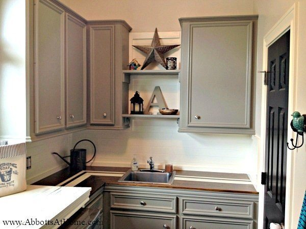 Dark grey cabinets with a DIY wood counter in a Laundry Room. This Modern Farmhouse DIY Laundry Room Makeover Ideas post is full of Before & After Makeover Photos, budget-friendly DIY ideas, and Laundry Room decor. #LaundryRoom #BeforeandAfter #AbbottsAtHome