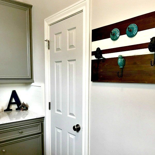 Dark grey painted cabinets, Quartz Counters and a DIY Wall Hook in the Laundry Room. This Modern Farmhouse DIY Laundry Room Makeover Ideas post is full of Before & After Makeover Photos, budget-friendly DIY ideas, and Laundry Room decor. #LaundryRoom #BeforeandAfter #AbbottsAtHome