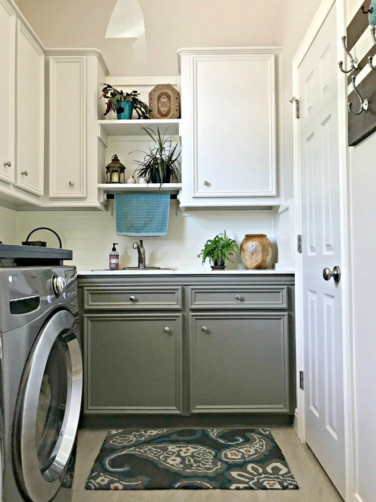 Creamy white cabinets and walls with grey lower cabinets, with plants, wood accents, and teal pops of color. This Modern Farmhouse DIY Laundry Room Makeover Ideas post is full of Before & After Makeover Photos, budget-friendly DIY ideas, and Laundry Room decor. #LaundryRoom #BeforeandAfter #AbbottsAtHome