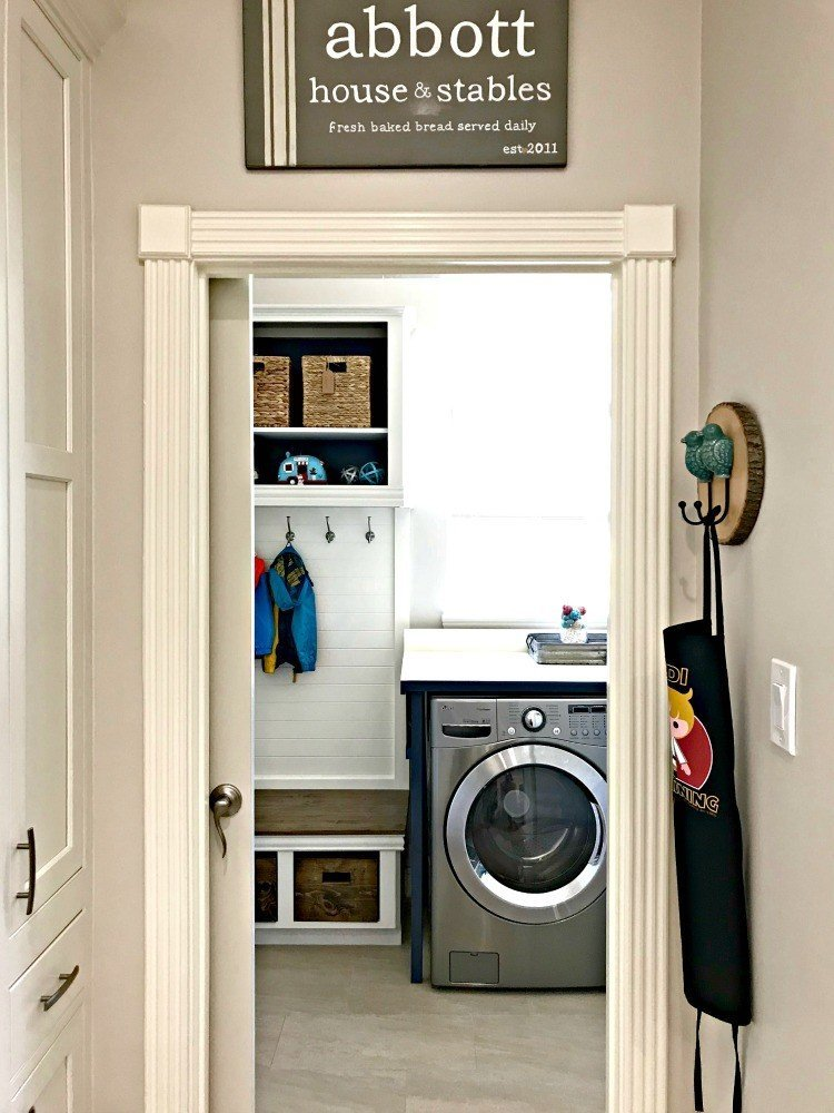 The view of our Laundry Mudroom Bench from the Kitchen. This Modern Farmhouse DIY Laundry Room Makeover Ideas post is full of Before & After Makeover Photos, budget-friendly DIY ideas, and Laundry Room decor. #LaundryRoom #BeforeandAfter #AbbottsAtHome