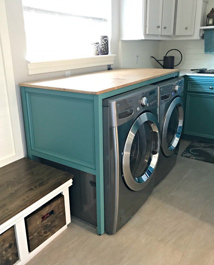 Add style and a great folding table to your Laundry Room with this over washer and dryer DIY Laundry Table. See the full tutorial and printable build plans. This simple build hides those ugly machines, adds extra style and organization. #LaundryTable #WoodworkingIdeas #DIYWoodworking #DIYFurniture #LaundryRoomIdeas #AbbottsAtHome