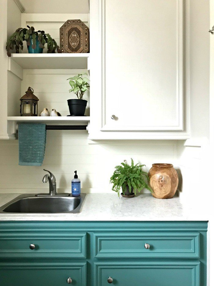 Wood decor and plants add style in this small room. A fresh Modern Farmhouse look using teal, wood, and lots of white. This Modern Farmhouse Small Laundry Room Design is full of easy DIY projects and affordable decor. #LaundryRoom #ModernFarmhouse #Teal #AbbottsAtHome