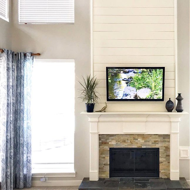 Shiplap above a traditional fireplace with a TV mounted above fireplace.