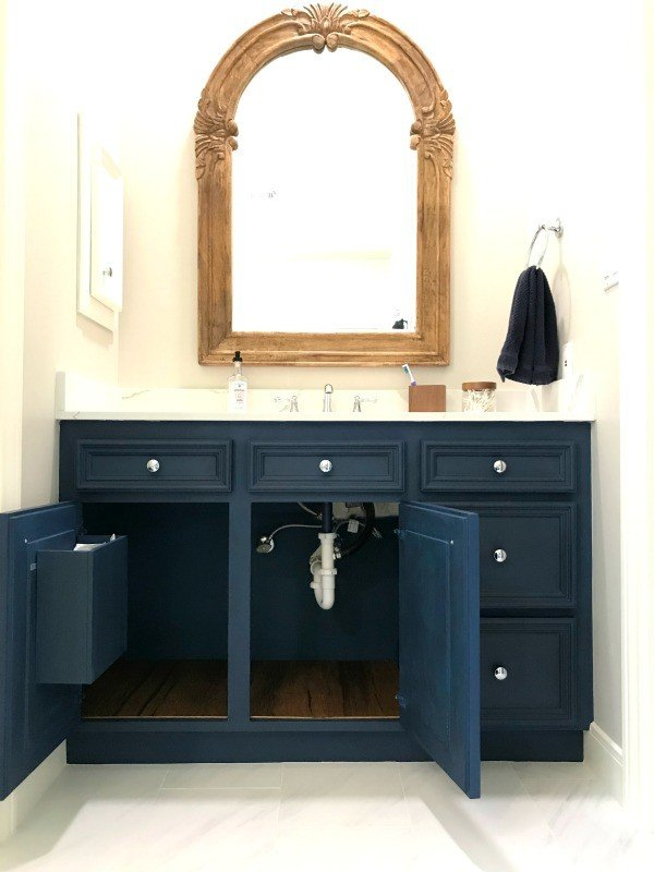 Dark Blue and Dark Wax Vanity Makeover with new stained plywood cabinet liners and a built in cabinet garbage can. See how she built the garbage can and find out about the makeover here. #AbbottsAtHome #BathroomMakeover #BathroomGarbage #BathroomOrganization #BathroomIdeas