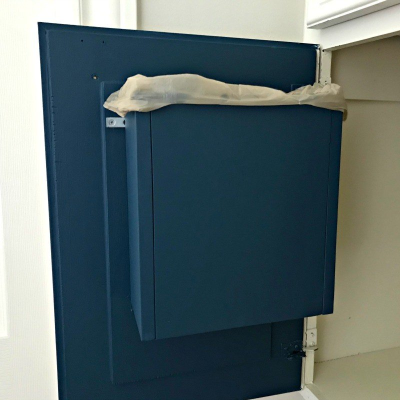 I love this bathroom storage idea! Hang your garbage can on the cabinet door with this DIY Cabinet Door Mounted Garbage Can Build Project.. This a quick and easy DIY win! #AbbottsAtHome #BathroomStorage #BathroomIdeas #DIYIdeas