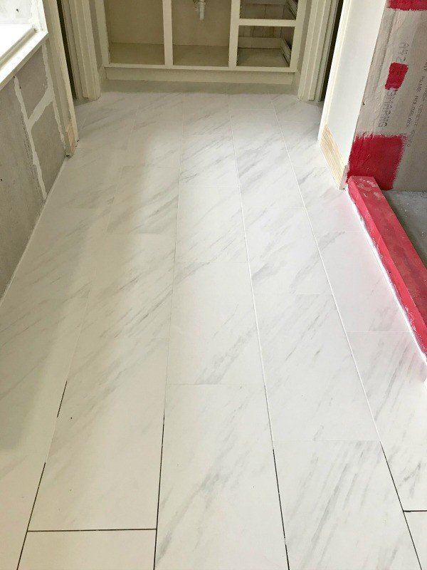 I'm loving this Marble Look Porcelain Tile, guys. The 12x24 size looks beautiful. The non-slip matte finish is pretty and perfect for a bathroom. Here are my DIY Tips for Installing Floor Tile Faster and Better. #AbbottsAtHome #MarbleLook #MarbleFloor #Tiling #Bathrooms