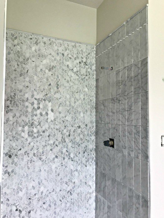 The outside edge of a walk in shower framed with Schluter trim and Bullnose Marble tiles. #AbbottsAtHome #MosaicTile #MarbleTile #BathroomTile