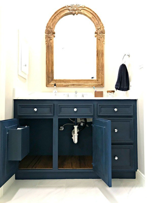 DIY Dark Blue Bathroom Cabinets with white counters and light walls.