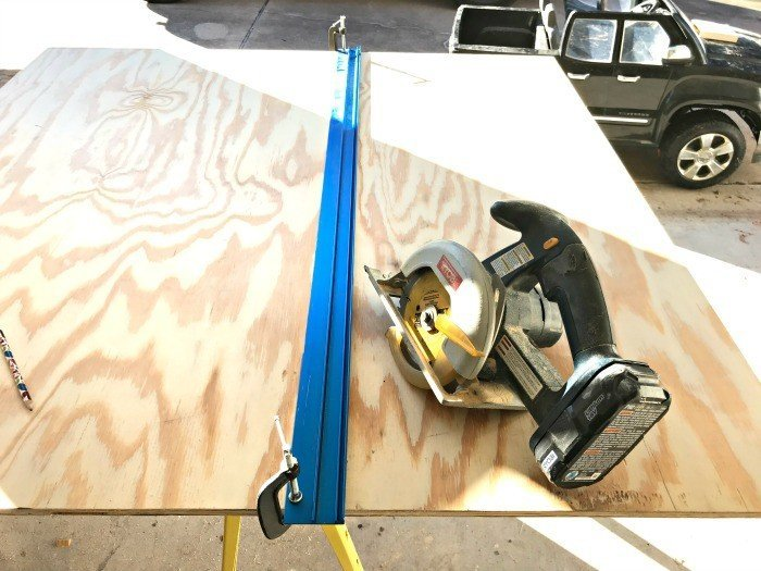 Using a straight edge cutting guide to cut plywood.