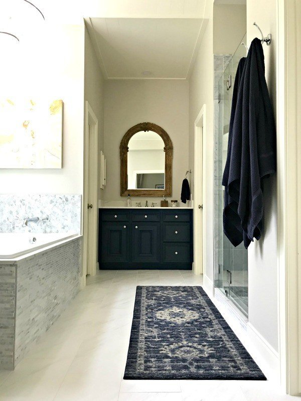 Yay! Our Bathroom Remodel is finished and I finally get to share all of the Before and After Master Bathroom Remodel photos with you guys.  This bathroom remodel features Marble Tile, Quartz Counters, Dark Blue vanities and a traditional style with classic design details. #AbbottsAtHome #MasterBathroom #BathroomRemodel #BathroomIdeas #InteriorDesign #BathroomDesign