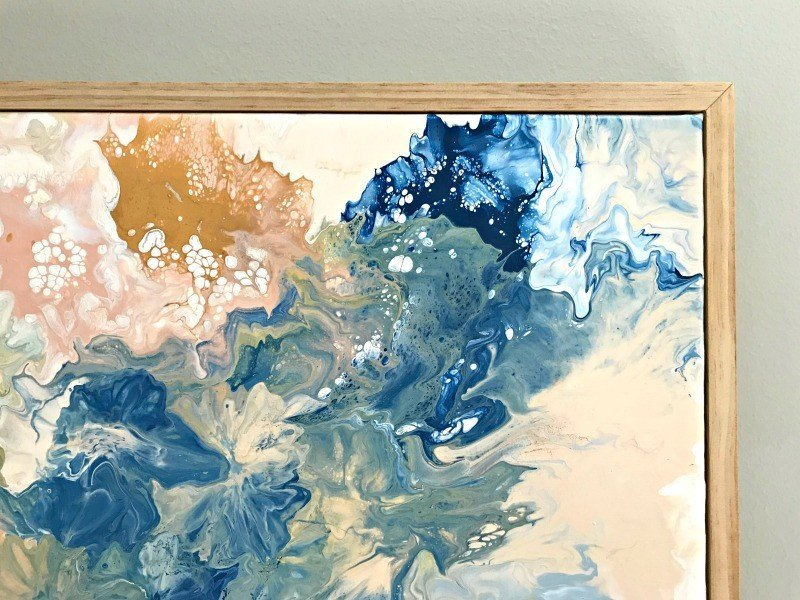 A close up of a DIY paint pour using acrylic paint. Click to see steps and how to video. #AbbottsAtHome #AcrylicPaint #AcrylicArt #Canvas #ArtIdeas #WallArt #DIYDecor #HandmadeArt