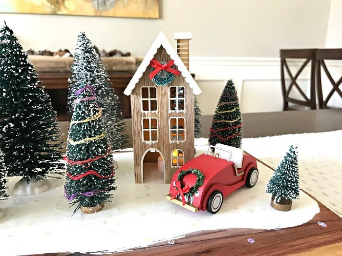 How to make this fun DIY Christmas Table Centerpiece with mini Christmas houses, bottle brush trees, and vintage red truck, camper, and car. DIY Red Truck Christmas Table Centerpiece. #AbbottsAtHome #CraftIdeas #CraftProjects #ChristmasProjects #ChristmasDIY