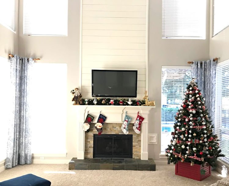 White Farmhouse Living Room with pops of color, decorated for Christmas. Shiplap Fireplace.