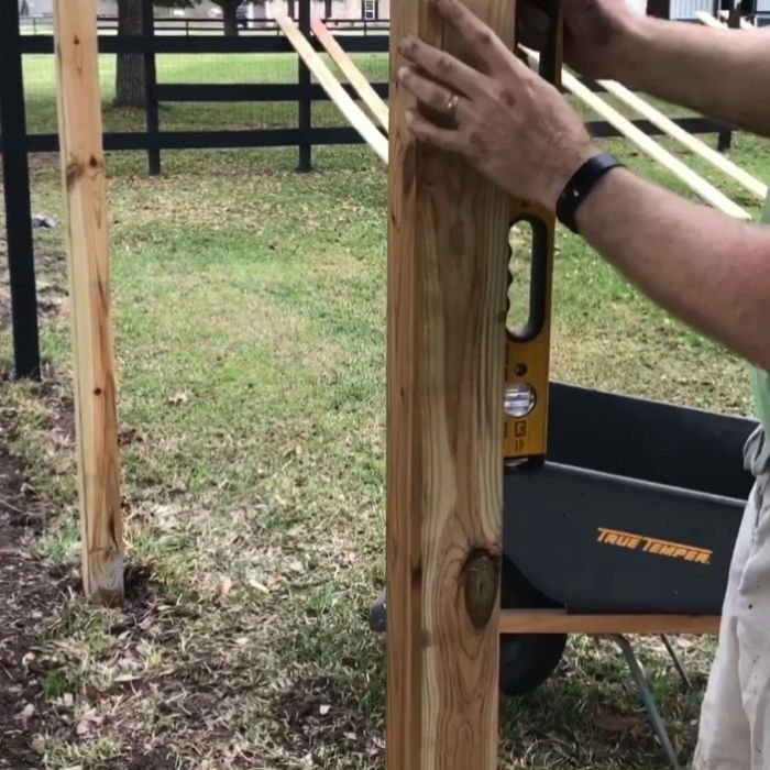 Using a spirit level to make sure a wooden fence post is straight.