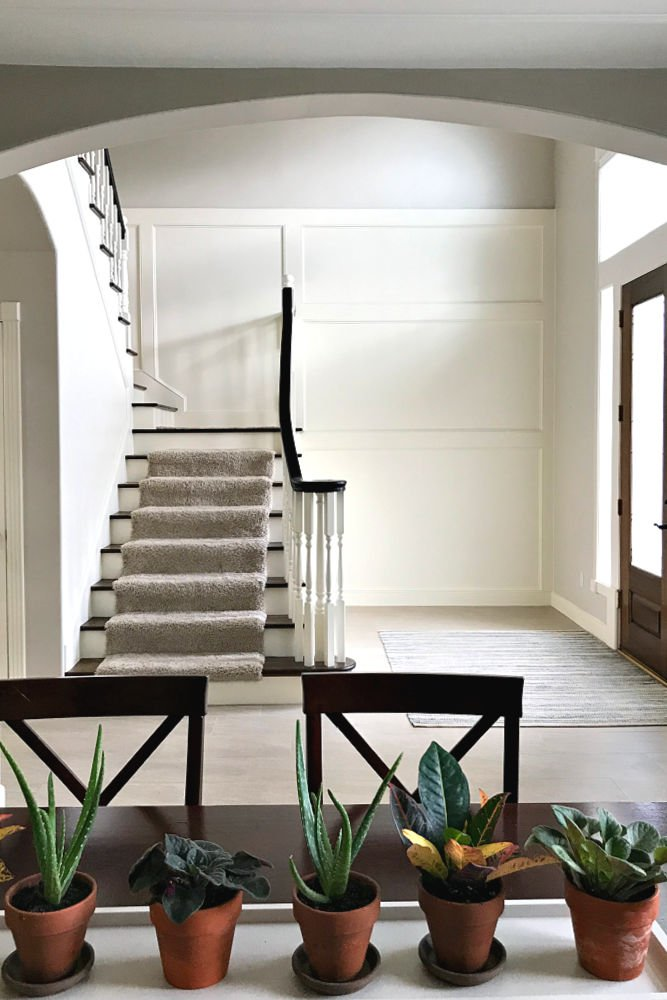 A white foyer with traditional stairs and with wood trim finish carpentry.